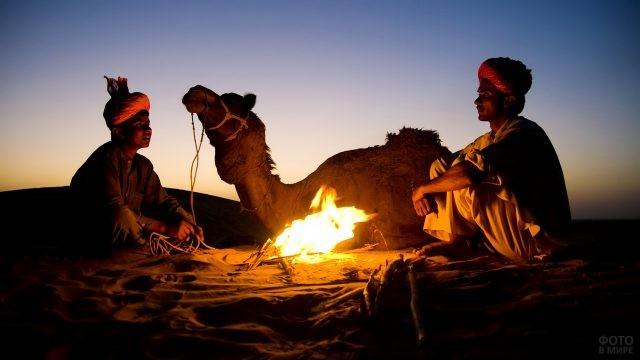 Бедуины с верблюдом в пустыне у ночного костра