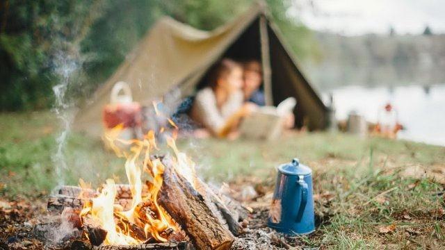 Костёр и чайник на фоне туристов в палатке