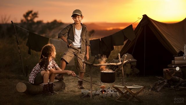 Мальчик и девочка в туристическом походе у костра и палатки