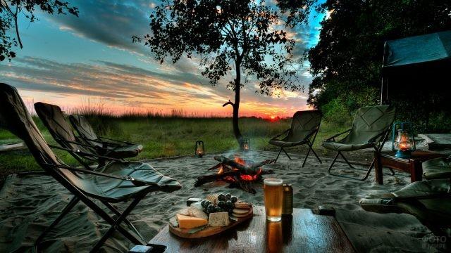 Место для отдыха на природе с кемпинговой мебелью и костром