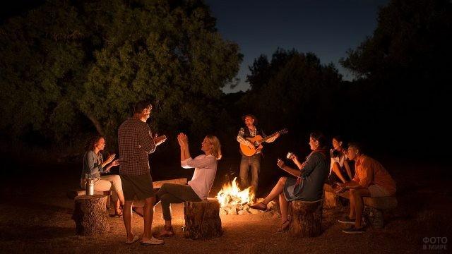 Отдыхающие люди с гитарой вокруг ночного костра
