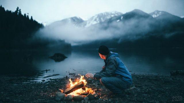 Турист у ночного костра возле горного озера
