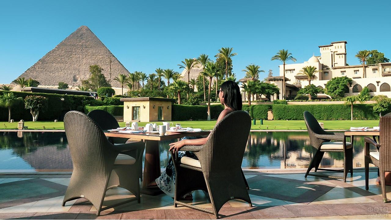 Туристка в ресторане пятизвёздочного отеля любуется на пирамиду Хеопса