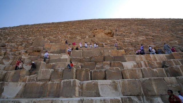 Туристы на каменных блоках пирамиды Хеопса