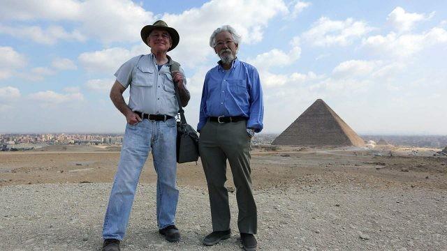 Учёные-археологи на фоне пирамиды Хеопса над панорамой Гизы
