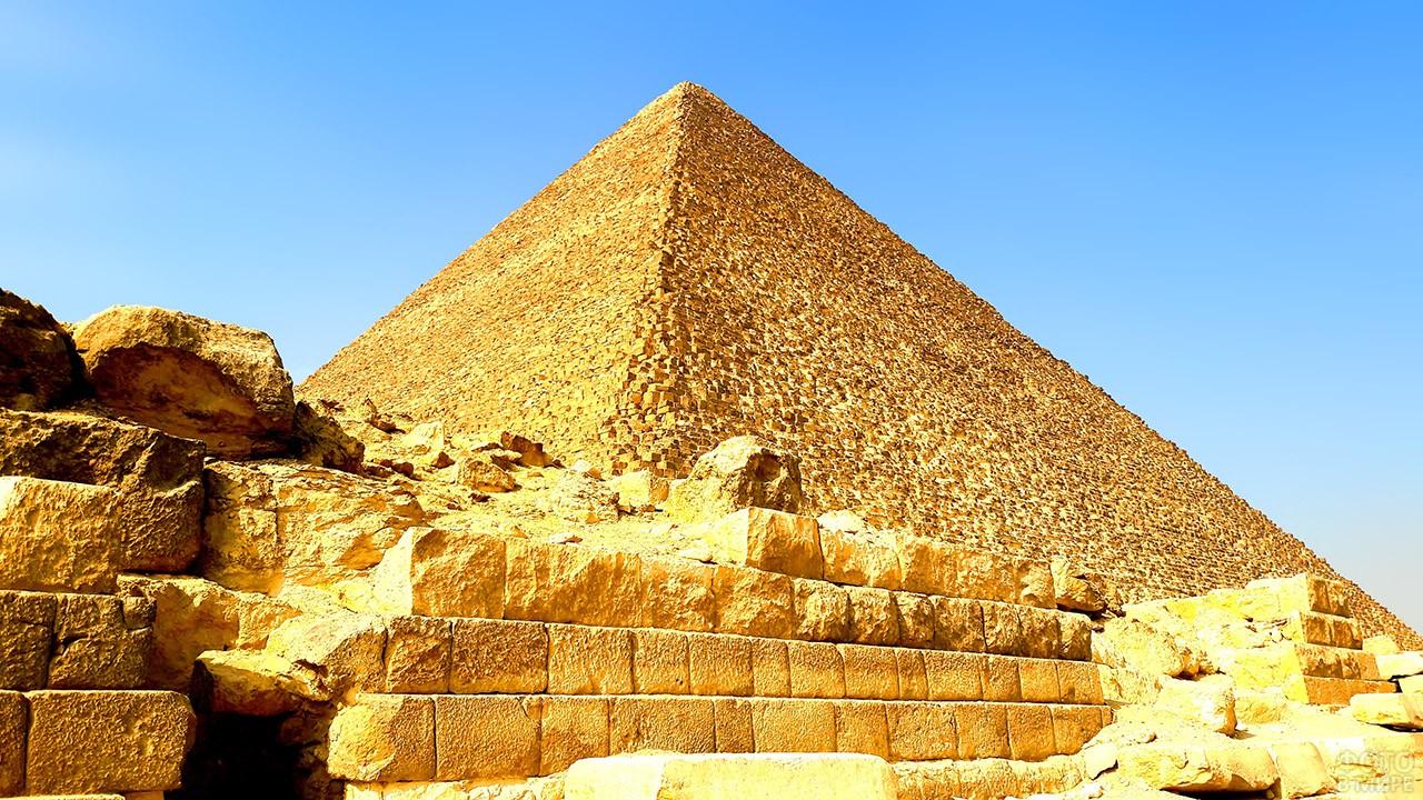 Золотистая кладка египетской пирамиды на фоне ясного голубого неба