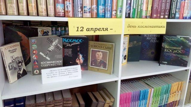 Библиотечный стенд к Дню космонавтики с книгами о покорителях космоса