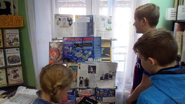 Дети у стенда к Дню космонавтики в школьной библиотеке