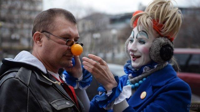 Аниматор надевает на прохожего клоунский нос 1 апреля