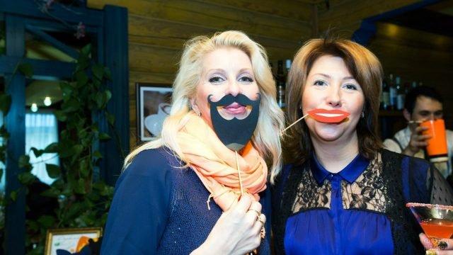 Дамы с бумажными усами и улыбкой на палочках на первоапрельской вечеринке