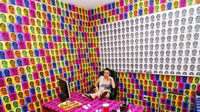 Девушка на рабочем месте с множеством разноцветных портретов босса к 1 апреля