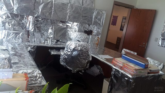 Обмотанные фольгой стол и предметы в кабинете шефа на 1 апреля