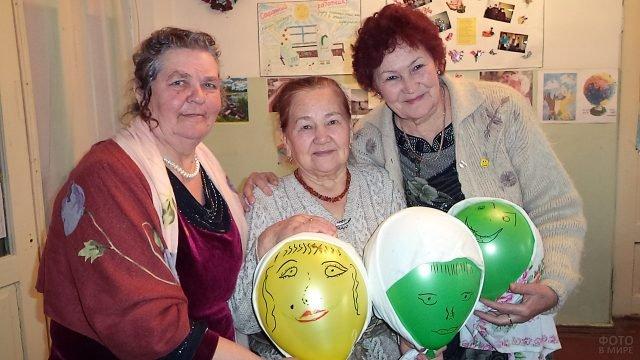 Пенсионерки с портретами на воздушных шариках отмечают 1 апреля