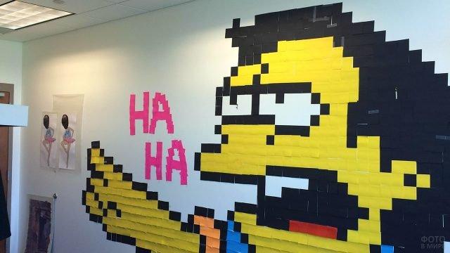 Персонаж из мультфильма выложенный стикерами на стене офиса к 1 апреля