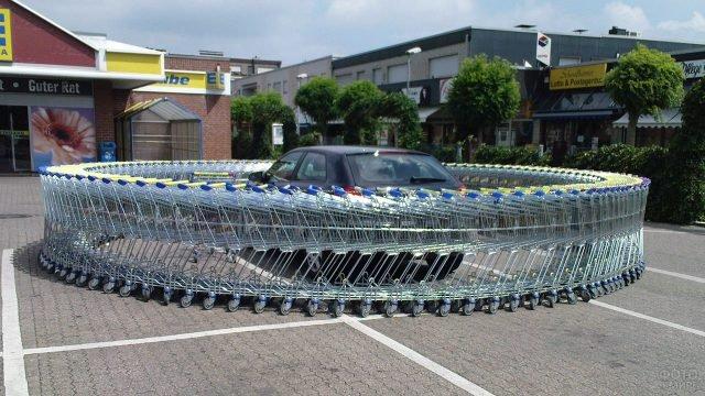 Первоапрельский прикол с окружённой тележками машиной у супермаркета