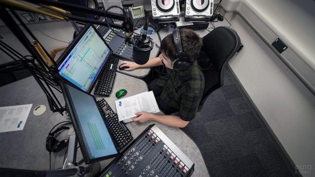 Молодой ведущий эфира в студии музыкальной радиостанции