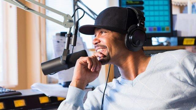 Радиоведущий в кепке и наушниках перед микрофоном