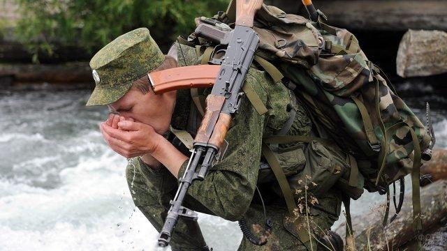 Солдат-пограничник пьёт воду из ручья во время марш-броска