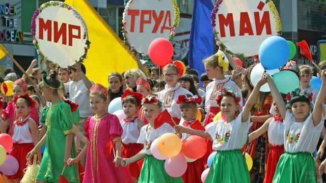 Дети в национальных костюмах и лозунги Мир-Труд-Май во главе колонны демонстрантов