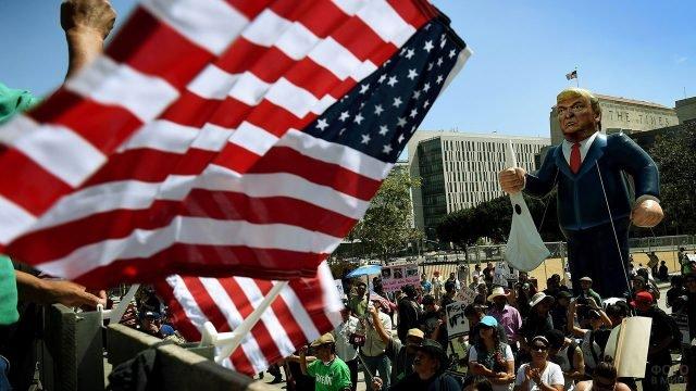 Надувной Трамп и звёздно-полосатые флаги на демонстрации Мэй Дэй в Америке