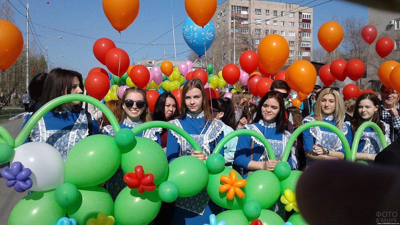 Нарядные школьницы с воздушными шариками среди демонстрантов на 1 мая