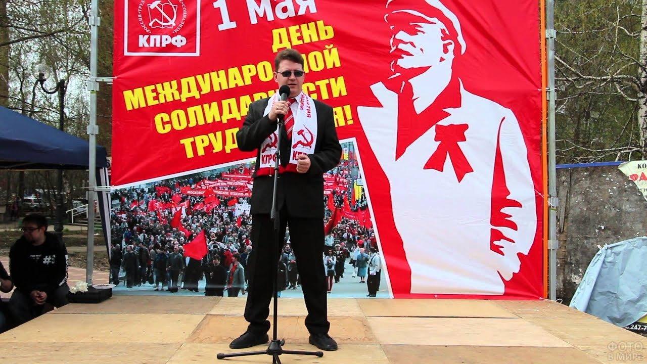 Ведущий на фоне первомайского плаката