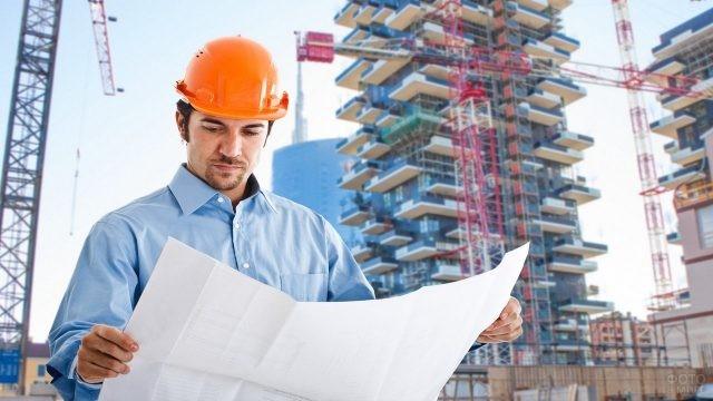 Архитектор на стройке с ватманом в руках