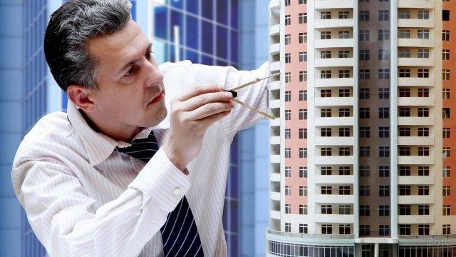Архитектор с циркулем измеряет макет