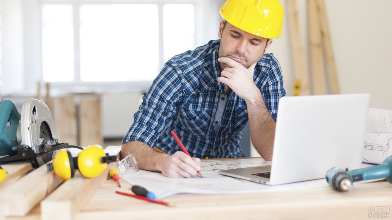 Архитектор в каске за ноутбуком и чертежами