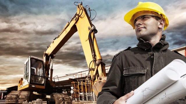 Суровый парень на строительстве объекта на фоне экскаватора