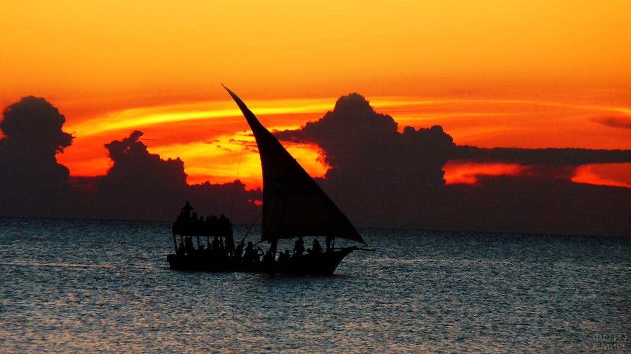 Силуэт туристической лодки на фоне заката