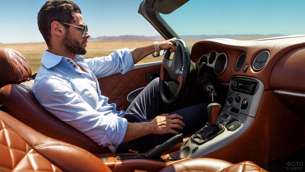 Мужчина в белой рубашке за рулём дорогого кабриолета