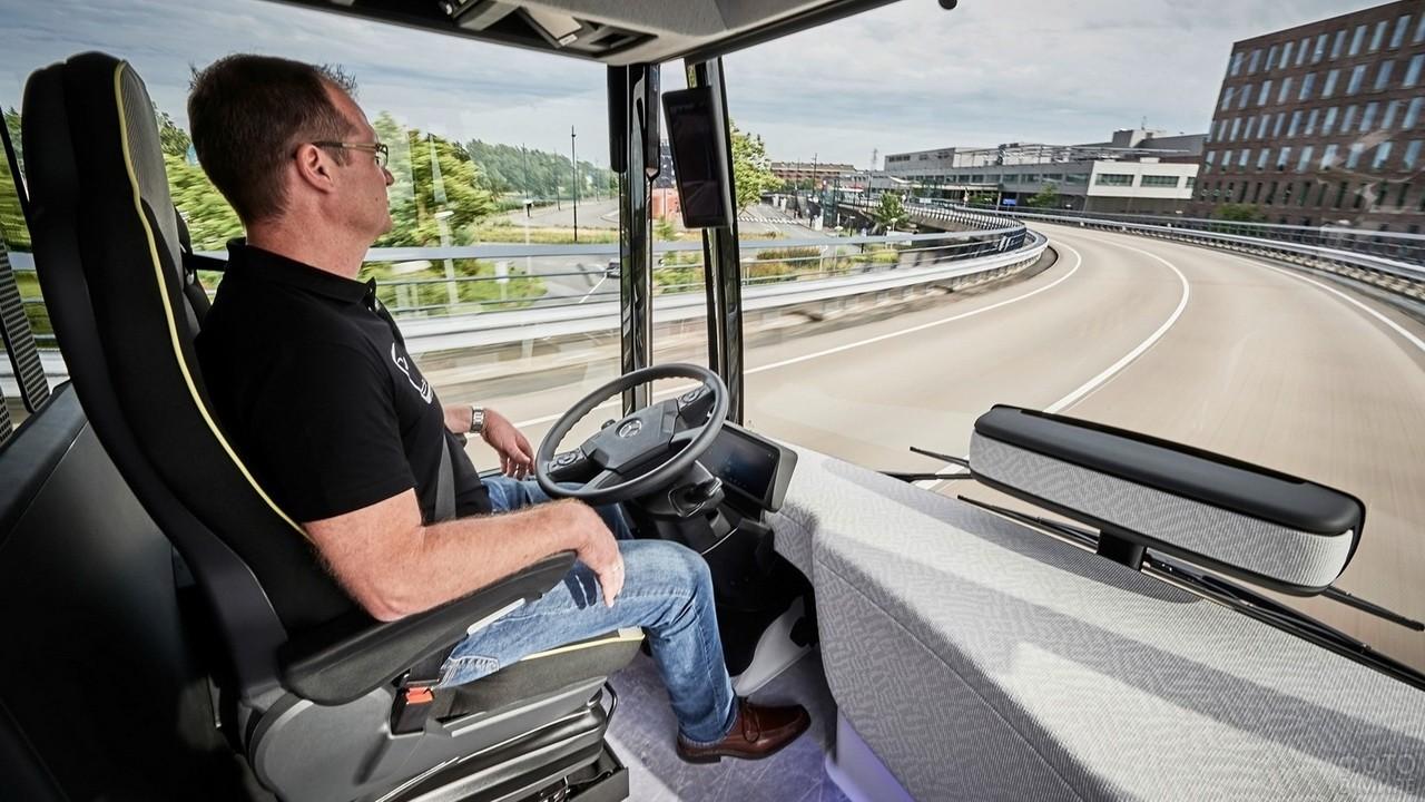 Мужчина в чёрной футболке за рулём грузовика на шоссе