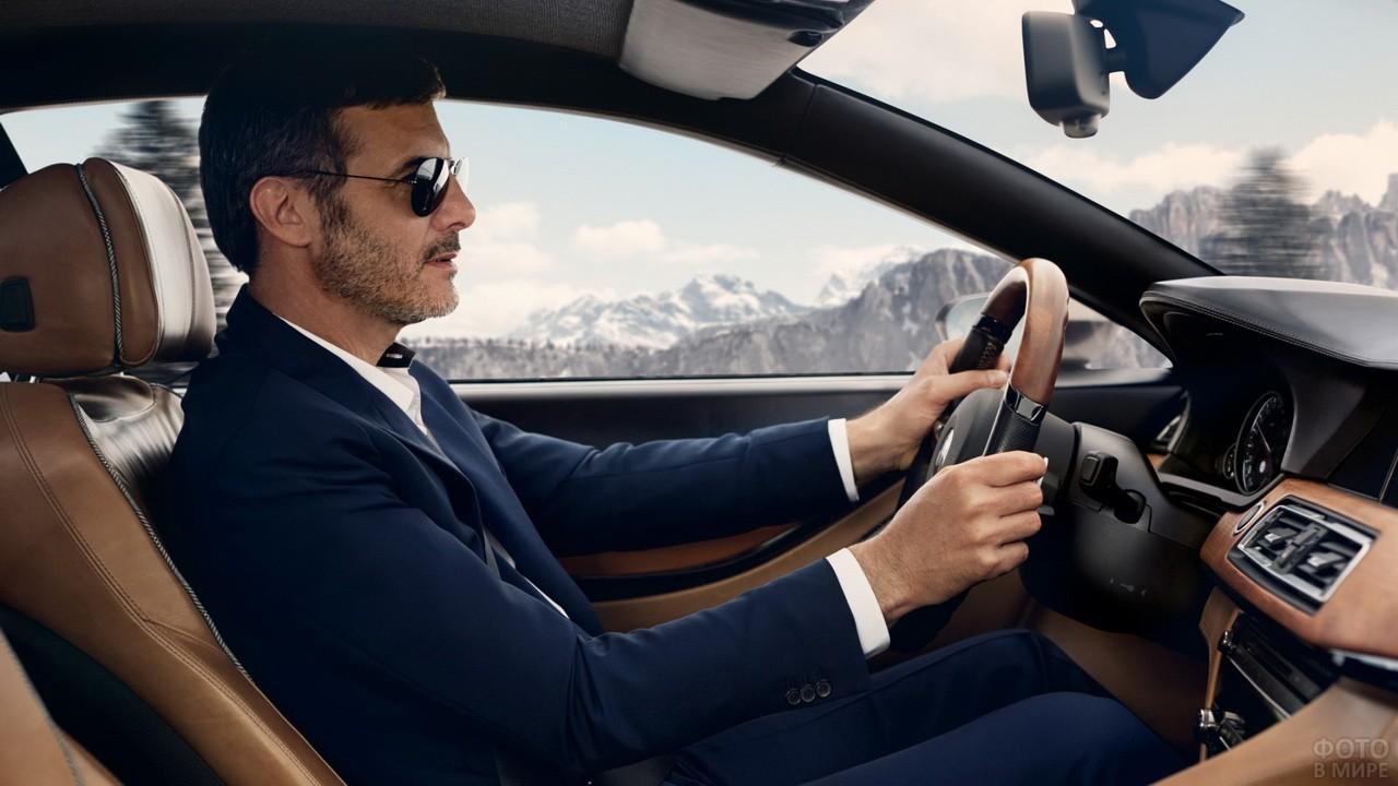 Мужчина в деловом синем костюме за рулём автомобиля