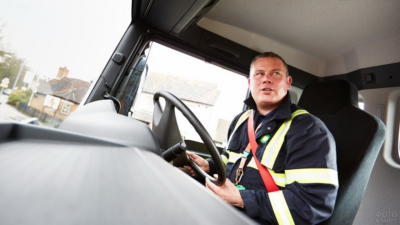 Мужчина в спецодежде за рулём грузовика
