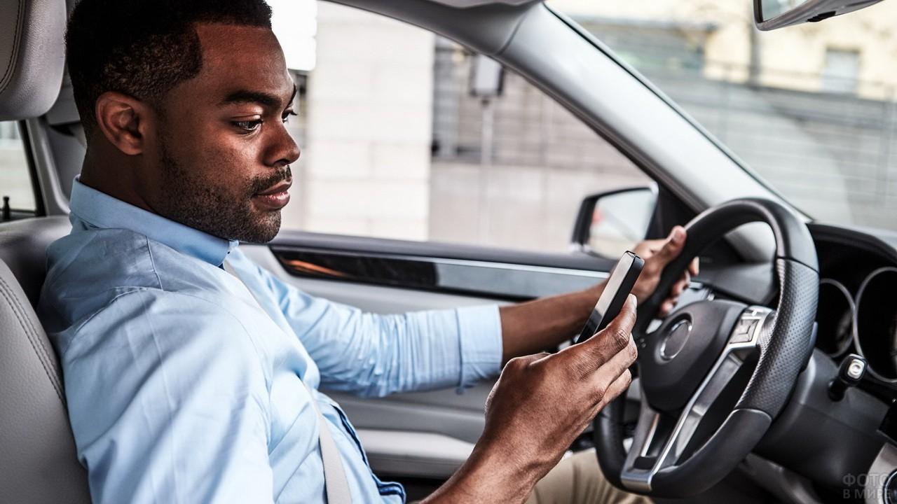 Негр за рулём автомобиля с телефоном в руке