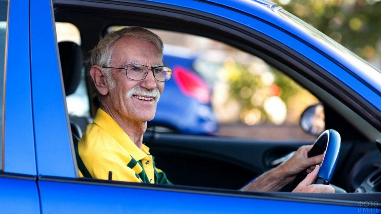 Пожилой мужчина за рулём синего автомобиля