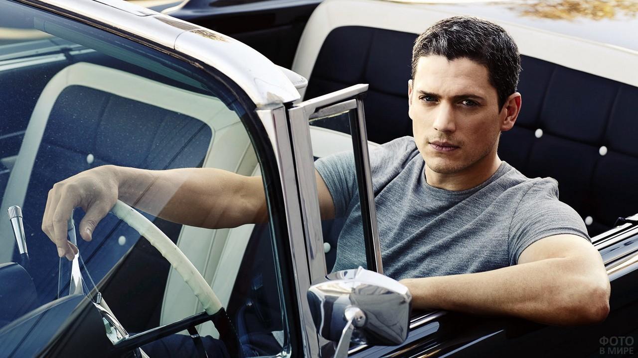 Серьёзный парень в серой футболке за рулём кабриолета