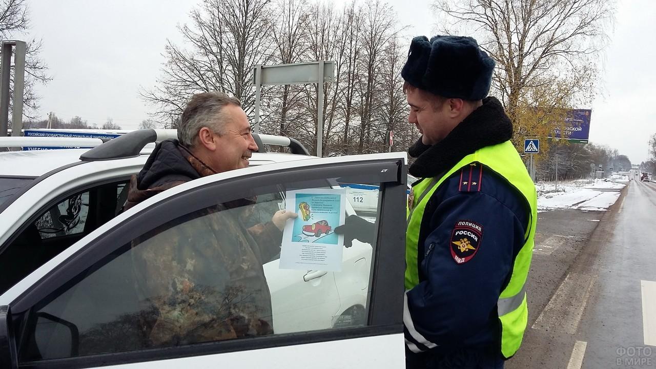 Сотрудник ГИБДД вручает памятку водителю