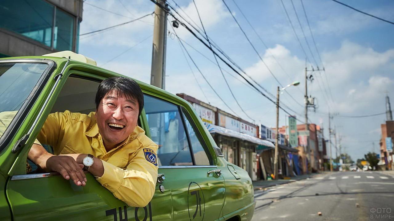 Таксист азиатской внешности в жёлтом костюме выглянул из окна такси