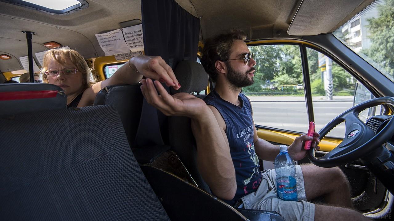 Водитель маршрутки в солнцезащитных очках берёт деньги за проезд