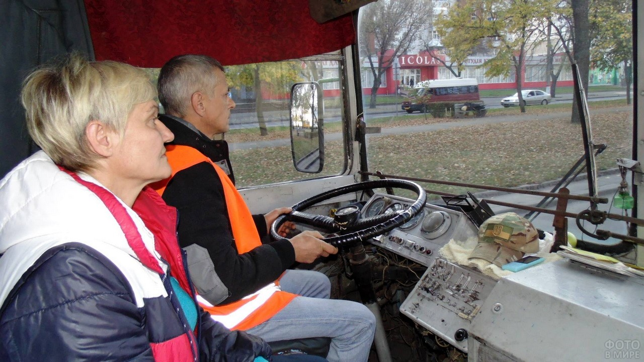 Водитель за рулём автобуса с сидящим рядом кассиром