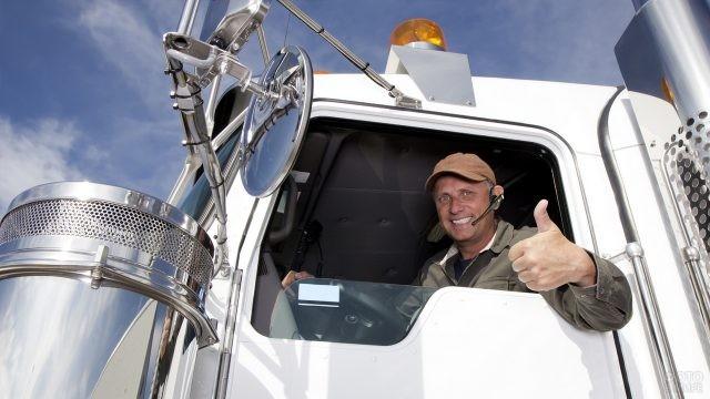 Водитель за рулём белого грузовика поднял большой палец вверх