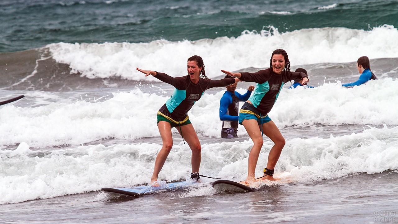Две девушки учатся в школе сёрфинга на Сардинии