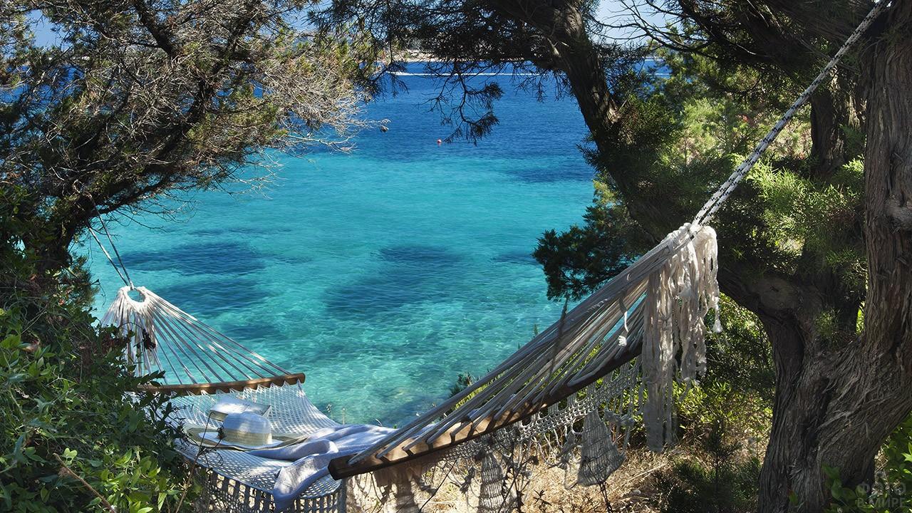 Гамак под тенистыми деревьями на побережье Сардинии