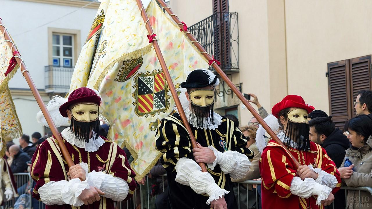 Венецианские маски на знаменосцах фестиваля Сартилье на Сардинии