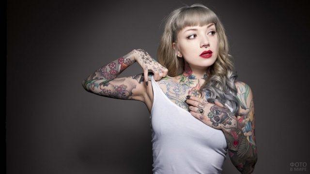 Девушка с кольцом в носу показывает татуировки на теле