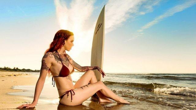 Девушка с тату на пляже с доской для сёрфинга