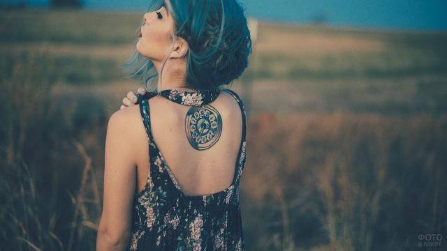 Девушка с татуировкой в виде часов на спине