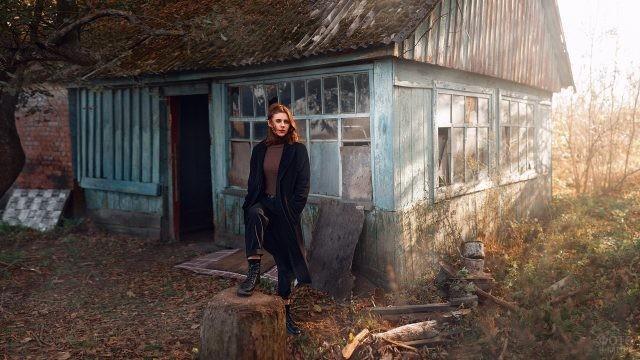 Девушка на фоне заброшенного синего дома